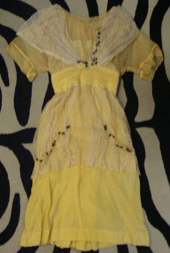 Teen girls afternoon dress from the early 1900s, in yellow silk. Built-in camisole on top, but is still rather sheer. The yellow is a bit muted in tone, but this is still brighter than pastel. Ivory lace bustle type overlay. Closes with hook/eyes in back. Certainly should fit a very small grown woman as well, actual dress measurements are as follows: Bust: 34 Waist: 24 Hip: 36 Length: 44 shoulder to hem, has been hemmed from original length. 2 of hem that could be let back out if needed ...