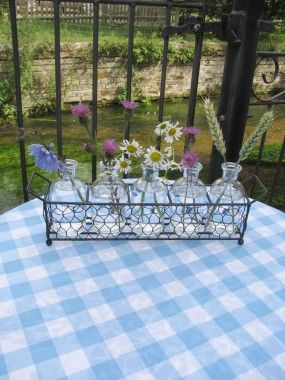 These five apothercary styled bottles and black mesh basket are perfect little vases for garden stems, making a pretty window cill display or for brightening a summer table.
