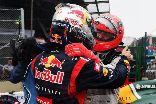 Sebastian Vettel of Germany and Red Bull Racing is congratulated by Michael Schumacher of Germany and Mercedes GP in parc ferme as he finishes in sixth position and clinches the drivers world championship during the Brazilian Formula One Grand Prix