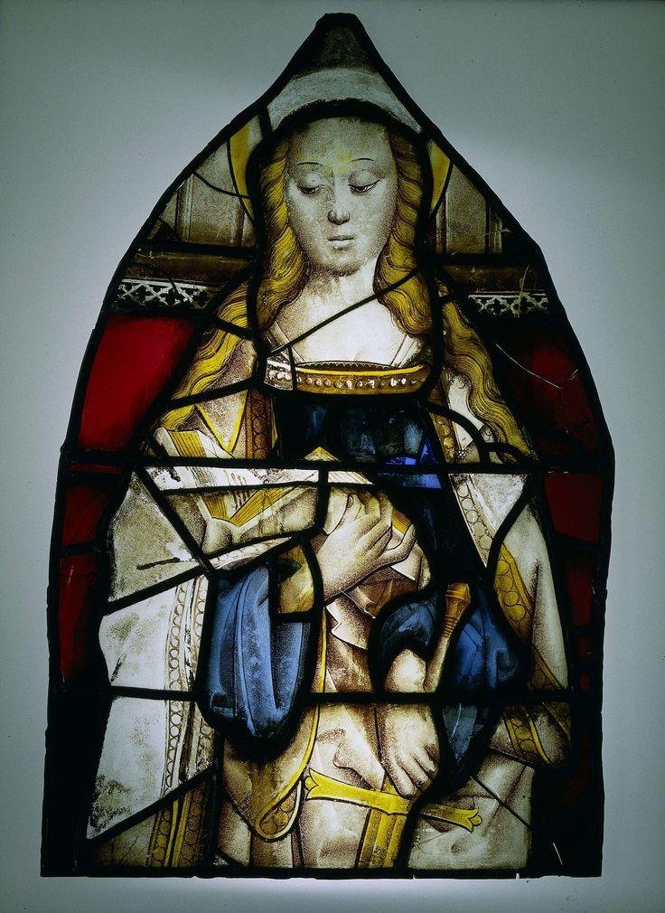 Anonymous   Ruit met de heilige Catharina, Anonymous, c. 1475   Ruit met gebrandschilderde voorstelling van de heilige Catharina. Catharina is frontaal weergegeven, lezend in een boek dat op haar rechterarm rust. Met de linkerhand omvat zij een zwaard. Om het hoofd een aureool. Op de achtergrond een rand van vierlobbige gotische ornamenten.