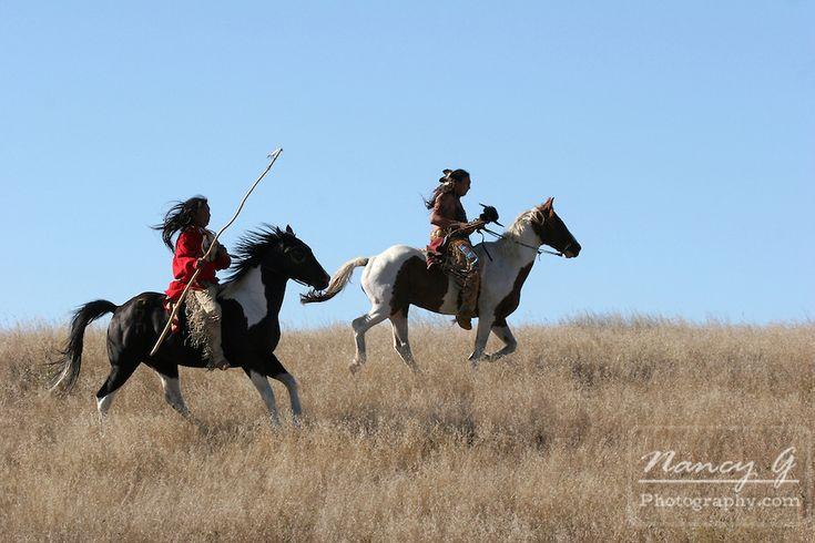 Two Native Americans riding horseback looking for ememies through the prairie of South Dakota. Nancy Greifenhagen Photography