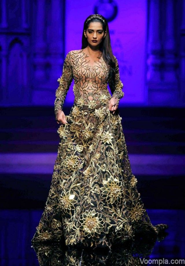 Sonam Kapoor walks the ramp for Abu Jani Sandeep Khosla in a black multi-panelled flared gown embellished with Swarovski crystals. via Voompla.com