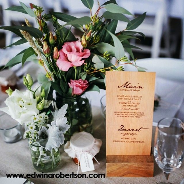Thanks to Amy and David for sharing this lovely photo from their wedding of their menu printed on mahogany wood held up by a clever little wooden block. #woodprints #printonwood #weddings #weddingmenus #realwood @edwinarobertson