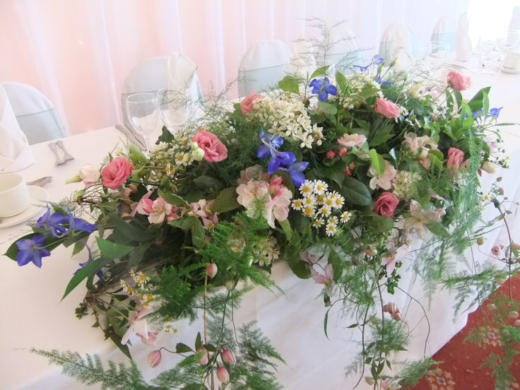 Top table arrangement from at May wedding at Henley Golf & Country Club in Henley-in-Arden, Warwickshire. A fragrant country garden combination of choisya (mexican orange blossom), feverfew, blue delphinium, double lisianthus and apple blossom with trails of asparagus fern and clematis.