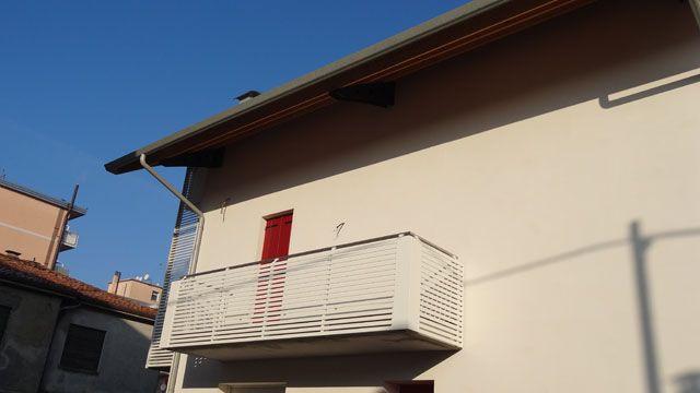 Parapetto terrazzo con montanti in ferro e dettaglio angolare in lamiera alluminio Ral 9010, corrimano rientrante in acciaio inox.