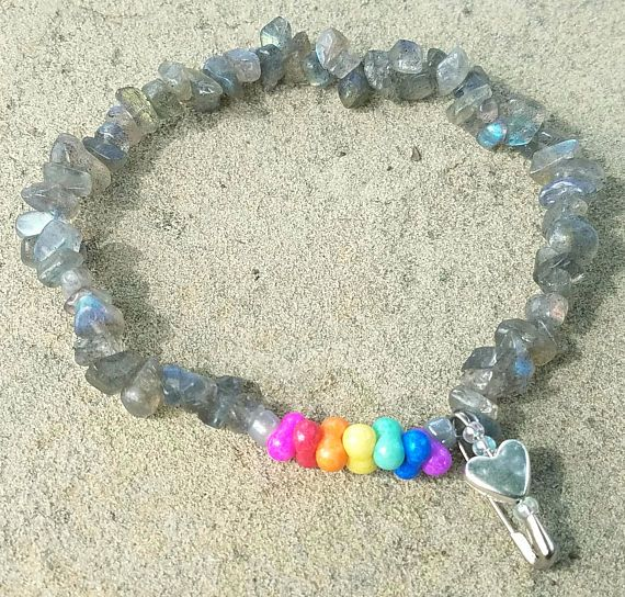 This 7 stretch bracelet is made with labradorite - an iridescent pale gray stone - and brightly colored rainbow stone beads. Attached is a small silver safety pin dangle decorated with a bright silver heart and iridescent seed beads. All proceeds benefit the Trevor Project:  http://www.thetrevorproject.org/  Founded in 1998 by the creators of the Academy Award®-winning short film TREVOR, The Trevor Project is the leading national organization providing crisis intervention and s...