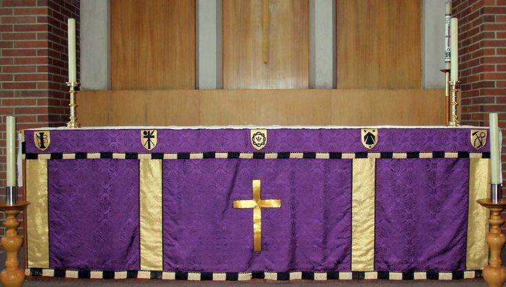 """St. Andrews Altar 4:  Church altar in Anglican church set up for Lent, with purple-and-gold altar cloth.  Altar cloth has symbols of the Crucifixion embroidered in gold and black.  Brick and wood walls, white candles in wood and brass candlesticks complete the background.  Image size 2550 x 1425px (300ppi); prints at 8.5 x 4.75""""."""