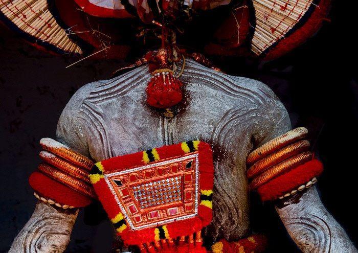 """hSvariate ore di trucco, uno spesso cerone steso sulla pelle, pesanti costumi fatti con noci di cocco colorate, ingombranti copricapi alti anche 6-7 metri. Non sono poche le """"torture"""" che gli esecutori del Theyyam, una danza rituale caratteristica dello stato indiano del Kerala, devono sopportare. Ma alla fine della lunga preparazione i loro sforzi sono ricompensati: durante il ballo gli artisti (qui un particolare del make-up della schiena) entrano in comunione profonda con la divinità (che…"""