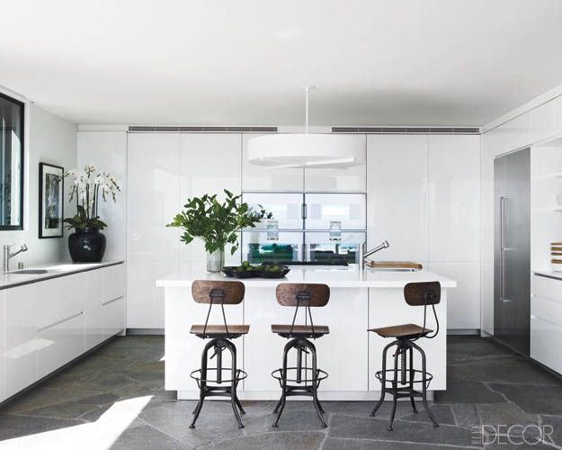 Courteney Cox's kitchen designed by Trip Haenisch features countertops by CaesarStone, ovens and a refrigerator by Gaggenau, and stainless-steel sinks by Franke in the main kitchen; the light fixture is from Nessen Lighting, and the barstools are vintage.