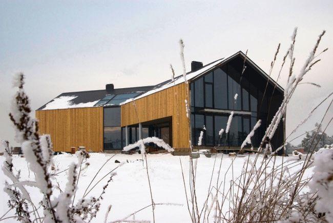 """Dom """"Złamana stodoła"""" w Bielanach Wrocławskich zaprojektowała Pracowni Architektoniczna Głowacki. Z jednej strony – nawiązanie do tradycyjnego, wiejskiego budownictwa, z drugiej – oszczędność środków wyrazu typowa dla współczesnej architektury. Jest to nakryta z zewnątrz dwuspadowym dachem, drewniana stodoła, której nowoczesnego sznytu dodaje przełamanie bryły w połowie jej długości i duże przeszklenia. Więcej na: http://sztuka-architektury.pl/index.php?ID_PAGE=20977"""