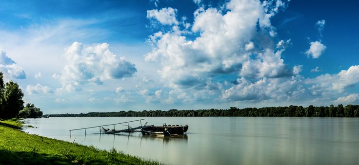 Danube Cloudscape - Clouds over the Danube. Panorama image from several captures with two different exposures. The exposure of the water is…