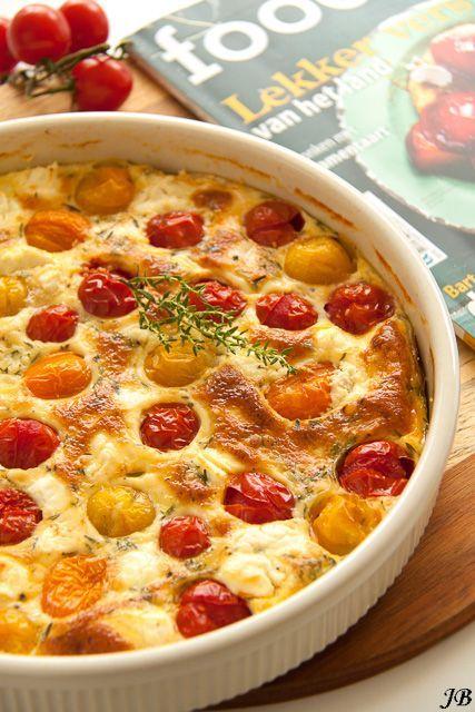Ingrediënten: - 120 ml melk - 120 ml slagroom - 500 g kerstomaten (verschillende kleuren) - boter om in te vetten - 4 eieren - 1 el bloem - zout en peper - 150 g zachte geitenkaas - een bosje tijm Ber