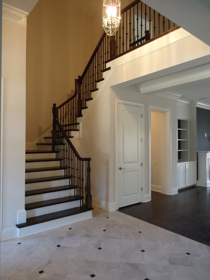 Natural stone foyer with wrought iron staircase ...