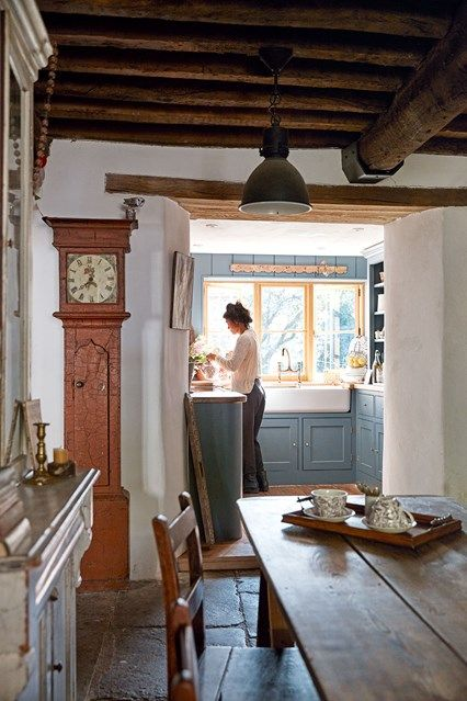 Rustic farmhouse kitchen in Kitchen Design Ideas - traditional kitchen with blue wooden units, butler sink, wood farmhouse table and antique grandfather clock.