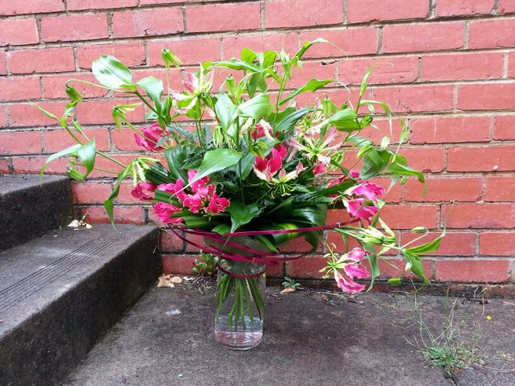Stunning bouquet of Gloriosa Lilies accented by tropical foliage & decorative wires