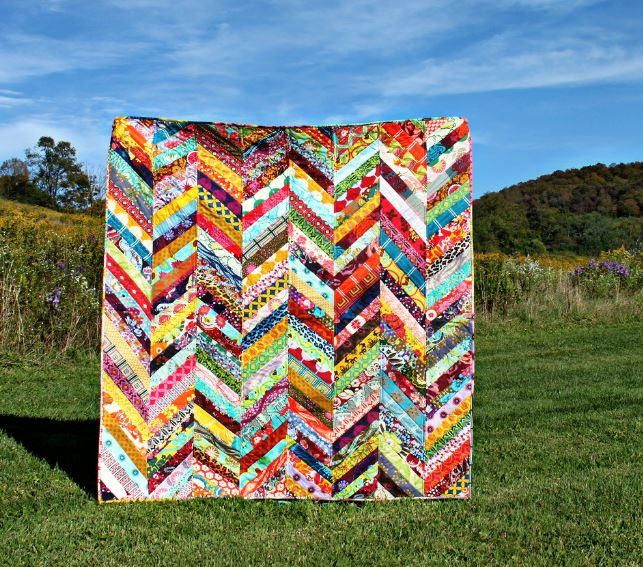 If your scrap pile has been building up lately, put those pretty fabric leftovers to good use with this Scrappy Herringbone Quilt Tutorial. You can create a brilliantly colored quilt quickly using this sew simple quilting tutorial that uses a traditional herringbone pattern. This easy quilting project goes together in long strips opposed to time consuming blocks, giving it a country chic look that's perfect for fall weather. The best thing about this quilt is that it's a <a hr...