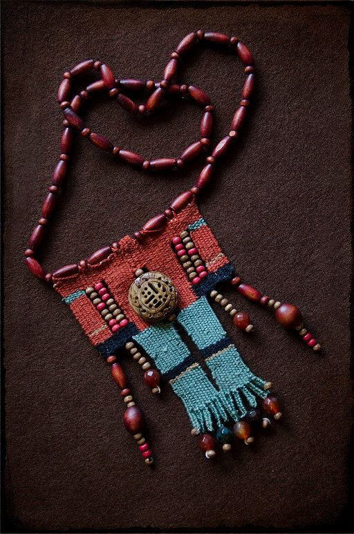 Ethnic handwoven necklace made with needleweaving technique with cotton threads on earthy colours and a big engraved wooden element in the