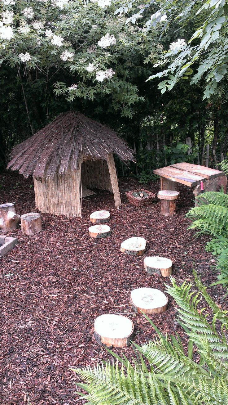 A fresh take on a children's play house - a DIY rustic roundhouse made from natural reed screening (walls) and a brushwood screening roof. The area also features a wooden table and chairs made from logs and timber planks. Designed and made by David Bennett