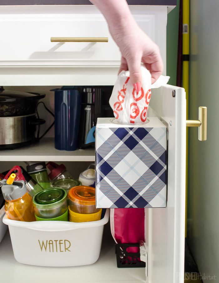 Attach an empty tissue box to the inside of a kitchen cabinet for easy-to-grab storage.