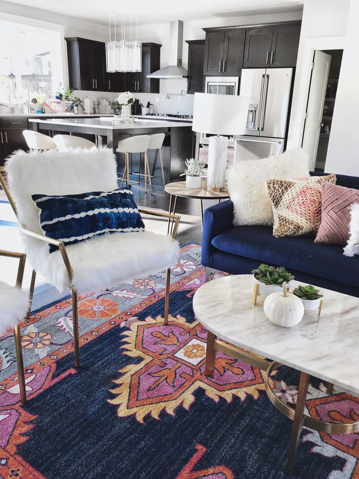 Modern Boho Chic Electric Living Room Gypsy Tan, Boho Rug kismet Ping Navy rug, Marble Coffee Table, Blue Couch, gold kitchen Stools