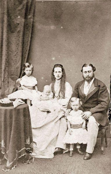 Familia Real Británica. (abajo) la princesa Louise en los brazos de su madre y el rey Jorge V, (arriba) el principe Alberto Victor, la reina Alexandra y el rey Eduardo VII del Reino Unido.