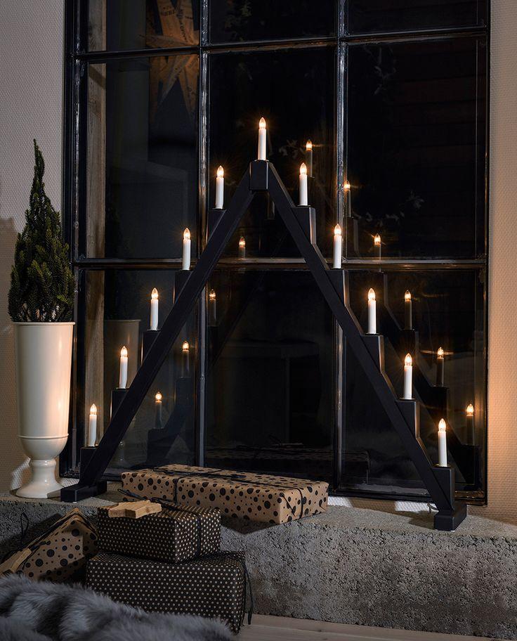 Stor adventsstake i sortlakkert treverk fra Konstsmide med klassisk trekantdesign med 11 hvite stavlamper og små dekorasjonsringer i messing. Staken er sammenleggbar og vil derfor være enkel å lagre.