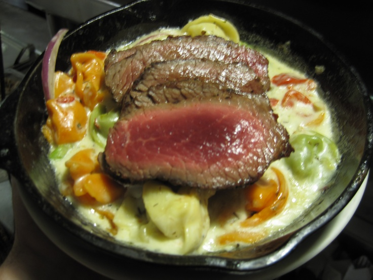 Bistro filet over cheese tortellini in a manchego mustard cream sauce. Be careful, the skillet is hot.
