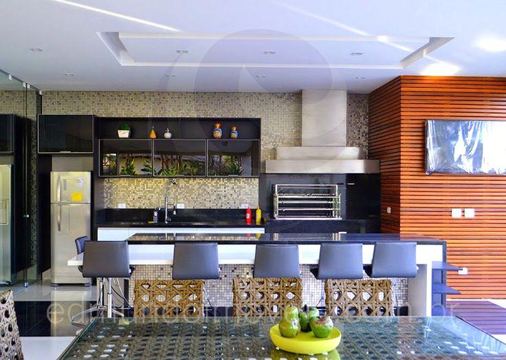 Divididos apenas por um vidro deslizante, ambos os ambientes contam com o mesmo padrão de acabamentos: paredes revestidas com pastilhas metálicas prateadas, bancadas em granito preto, armários planejados em preto glossy.