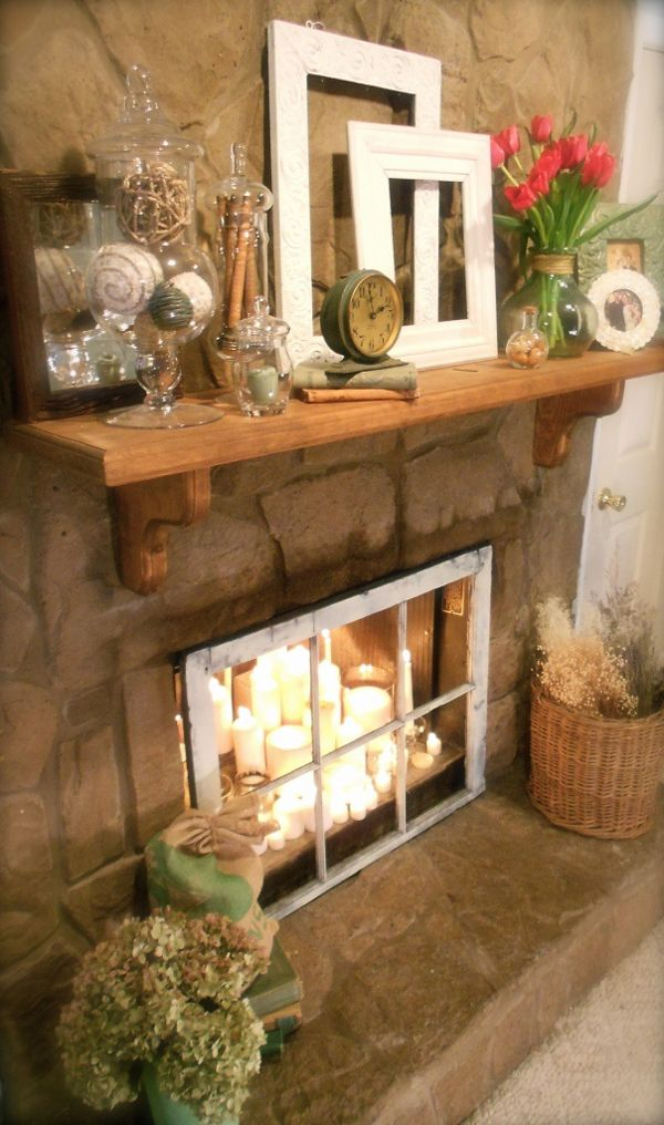 Rustic mantle over fireplace filled with candles, & an old window as screen.  So shabby, rustic.