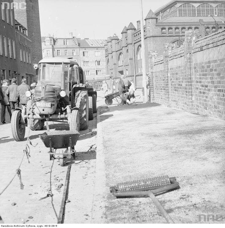 Wylewanie asfaltu na chodniku przy ulicy Pańskiej. Z lewej ciągnik Ursus C-4011. W oddali z prawej hala targowa.