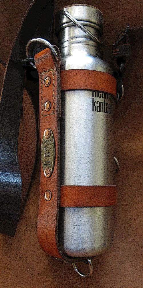 Klean Kanteen Leather Bottle Carrier. Fits all standard 27oz Klean Kanteens.  Made from thick, tough, vegtan cowhide. Dyed and hot-stuffed with waxes and oils. There are 12 hand-peened copper rivets used in its construction. Durable nickel horse-tack hardware and stitched with the best quality (durable!) thread. Comes with an adjustable vintage military leather strap with HK clips. This thing will go through a war!  This Klean Kanteen bottle carrier can snap anywhere onto your bag, belt loop…