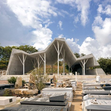 The thick folded concrete canopy of this structure in an Israeli graveyard is supported by slender tree-shaped columns that pay homage to a razed orchard