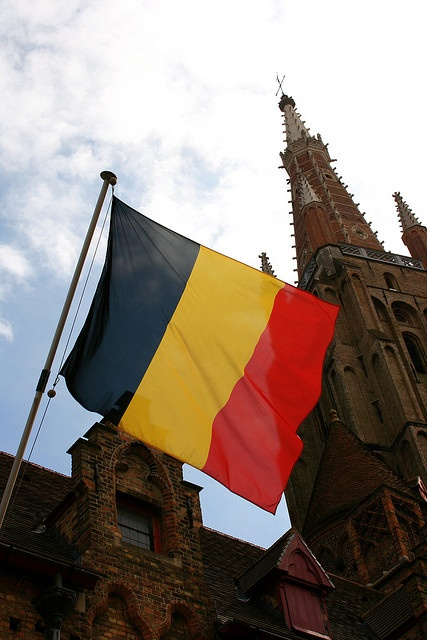The flag of Belgium in Brugge. Gruuthuse Museum and Onze-Lieve-Vrouwekerk in the Background