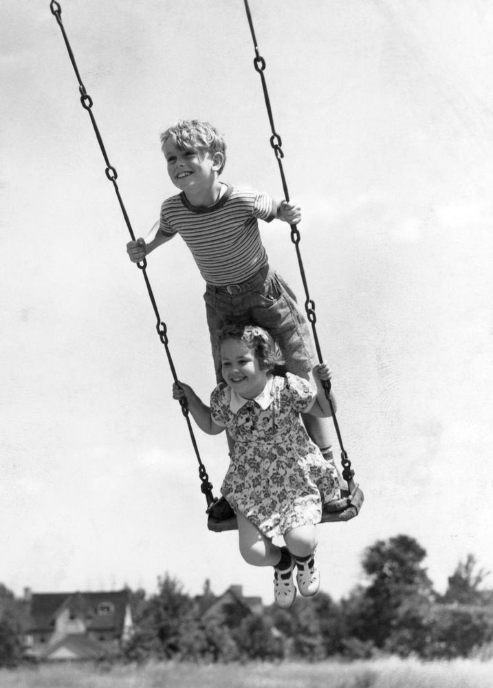 21 Glorious Vintage Photos Of Kids Having Fun Before The Internet | Circa 1930s: Boy And Girl On Swing.