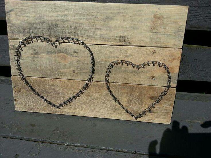 Van pallet hout ondergrond gemaakt....met spijkers vorm van hartjes en met ijzerdraad erom heen gedraaid