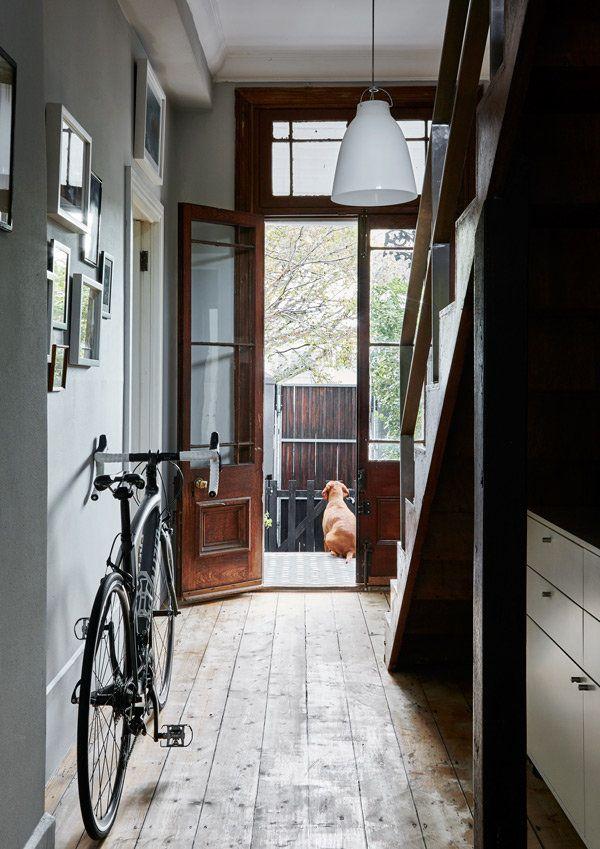 Una vista desde el comedor hacia el pasillo y la entrada a la casa.  La puerta delantera de madera y vidrio es de estilo victoriano y la escalera de madera, que se añadió durante la adición de la primera planta de la casa hace dos años, se mezcla perfectamente con los elementos del patrimonio existente de la casa.