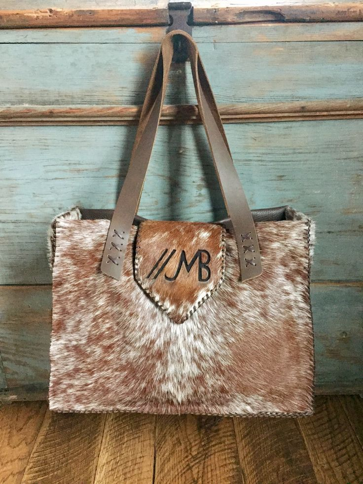 The Buckaroo Tote, stitched in brown leather lace with the owners brand in brown suede on the flap. Lined with two interior pockets.Custom purses and totes from gowestdesigns.us