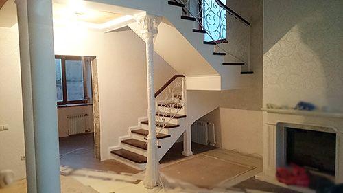 Полувинтовая лестница на центральном столбе с кованым ограждением