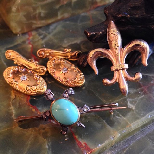 Victorian gold jewelry circa 1890a including fleur de lis watch holder, cufflinks with old mine cut diamonds and turtle turquoise pin with rose cut diamonds at The Antique Guild of Alex, Va.