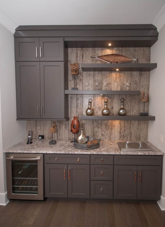 A contemporary gray home bar with open shelving and rustic paneling as a backsplash. The bar includes a wine fridge and a built-in ice bucket.