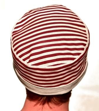 An ivory/chalk pill box hat with burgundy / merlot stripes and a lightly padded crown and a full white inner. Reversible and can be worn in a few different ways.  A fun modern pill box hat.  Circumference =  approx. 62cm Height unfolded = approx. 12cm