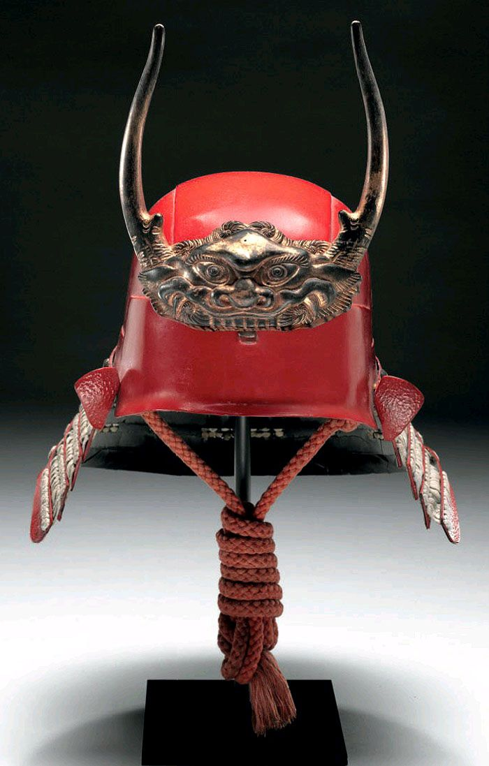 Hineno-style Kabuto. Edo period (18th-19th century) A red-lacquered five-plate Hineno-style zunari (head-shaped) kabuto, five-tier shikoro of itazane lacquered red in simulation of wrinkled leather, small fukigaeshi, the maedate (forecrest) of gilt wood in the form of a long-horned demonic  shishi