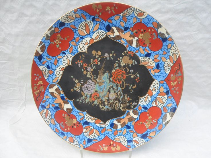 A 1920s Wood & Sons Bursley Ware large wall plaque, designed by Charlotte Rhead in the 1326 pattern, having a tube-lined decoration of stylized speckled fruits on a blue ground, the plaque inset with chinoiserie panels, some overpainted in red, designed by Horace Wain, depicting a bird and foliate bunches, printed and tubed marks verso, 41cm diameter