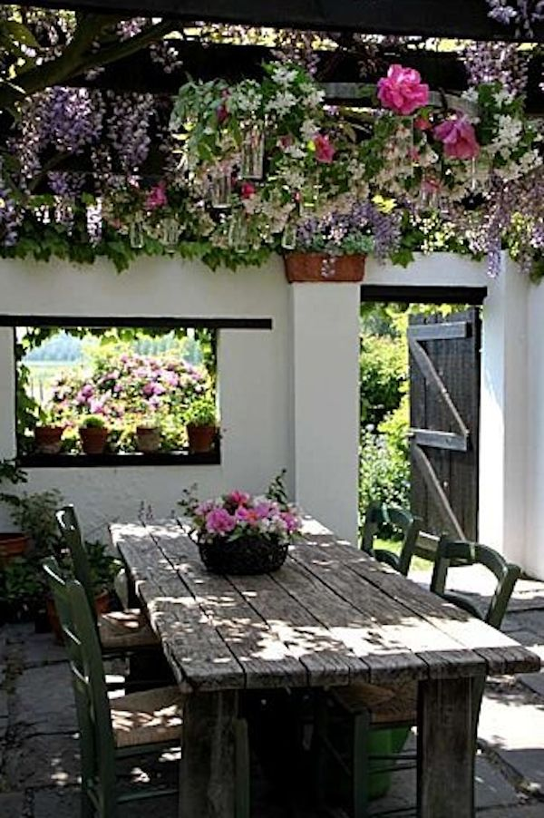 wisteria covered pergola,reclaimed wood table and the window carved into the wall....
