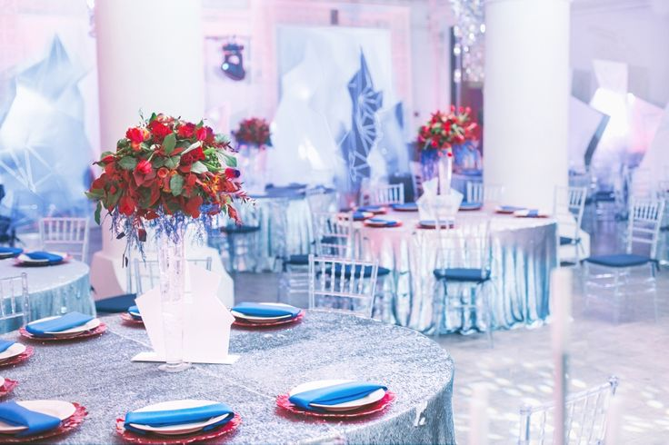 Оформление банкета в зимнем стиле. Периметр зала украшен белыми и серебряными декорациями в форме разнообразных снежных глыб, на столах серебряные пайеточные скатерти, прозрачные стулья, яркая флористика и сервировка