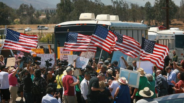 "Homeland Security buses carrying illegal immigrant were rerouted Tuesday to a facility in San Diego after American flag-waving protesters blocked the group from reaching a suburban processing center. The standoff in Murrieta came after Mayor Alan Long urged residents to complain to elected officials about the plan to transfer the Central American illegal immigrants to California. Many protesters held U.S. flags, while others held signs reading ""stop illegal immigration,"" and ""illegals out!"""