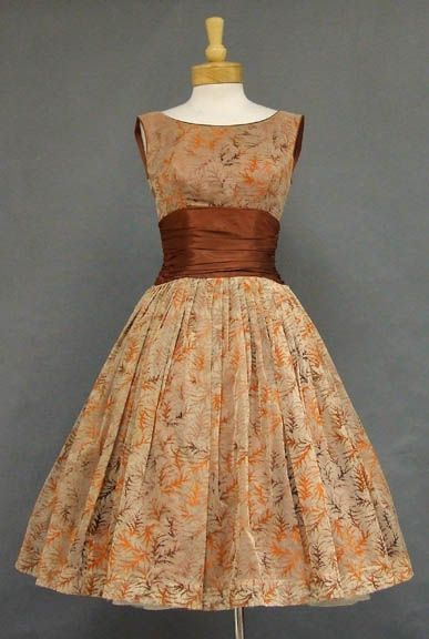 """A wonderful late 1950's/early 1960's cocktail dress in a tan nylon chiffon with orange to brown flocking. Fitted, sleeveless bodice with high neck, """"V"""" back and gathered sepia acetate waistband. Dress has a full skirt with an attached, but limp crinoline (shown here with an additional crinoline... not included). Lined in sepia acetate. Rear metal zipper."""