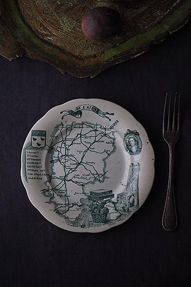 シリーズ、フランス地図エーヌ県-french porcelain plate パリより北東、ベルギーに繋がる土地。右上の人物は詩人でイソップ寓話詩で有名なジャン・ド・ラ・フォンテーヌ、同県シャトー=ティエリ生まれ。1885年のクレイユモントロー窯の品で、この時代のエーヌ県地方特産物であるアーティチョークや木綿生地も表示したトランスファープリントのお皿。上に盛る、例えばトマトやチーズの端に見えるパターンに「おや?」と思わせるユニークな仕立て。チップやヒビは御座いませんが、薄く茶色い点染みが御座います。見込みのサイズはw130mmです。