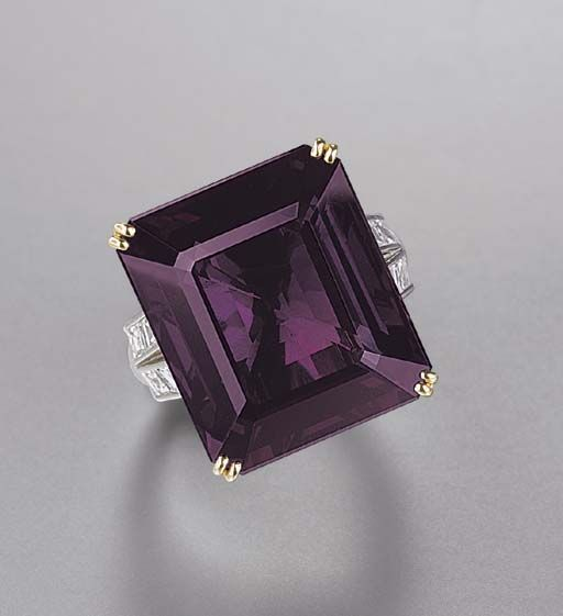 GABRIELLE'S AMAZING FANTASY CLOSET | An Alexandrite and Diamond Ring. The rectangular-cut alexandrite weighing 24.25 carats to the square-cut diamond bifurcated shoulders, mounted in platinum and 18k gold |