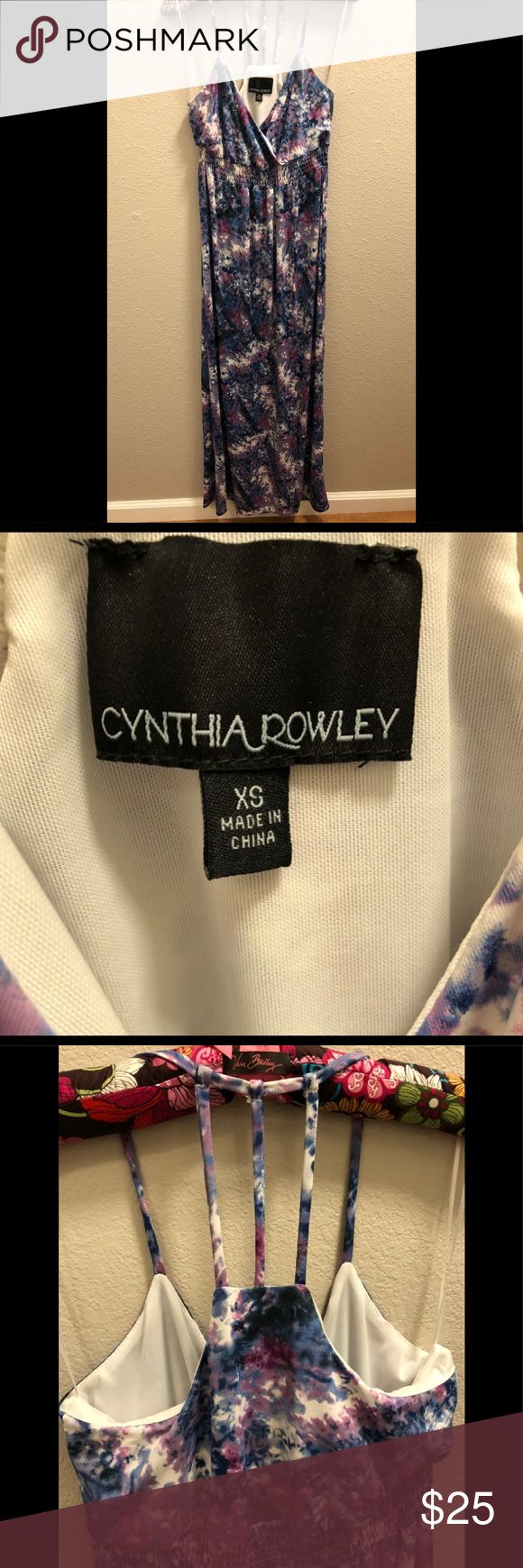 Cynthia Rowley Racerback Maxi Dress Cynthia Rowley Maxi Dress It has a lovely watercolor-inspired print in blue, purple and white, with a smocked, elasticized empire waistband which flows down to a full length.  The bust has a faux wrap style which mirrors the faux wrap style of the skirt.  Size is XS   *There is a stain in the inside of the top of the dress as shown in one of the pictures* Cynthia Rowley Dresses Maxi